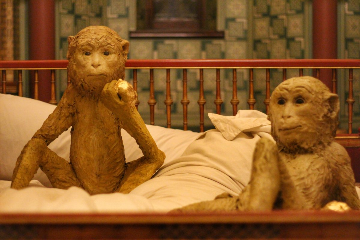 Two monkey sculptures on a bed
