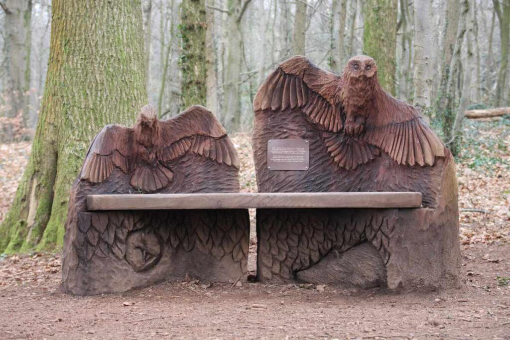 Wooden sculpture of a bench with a bird on each end