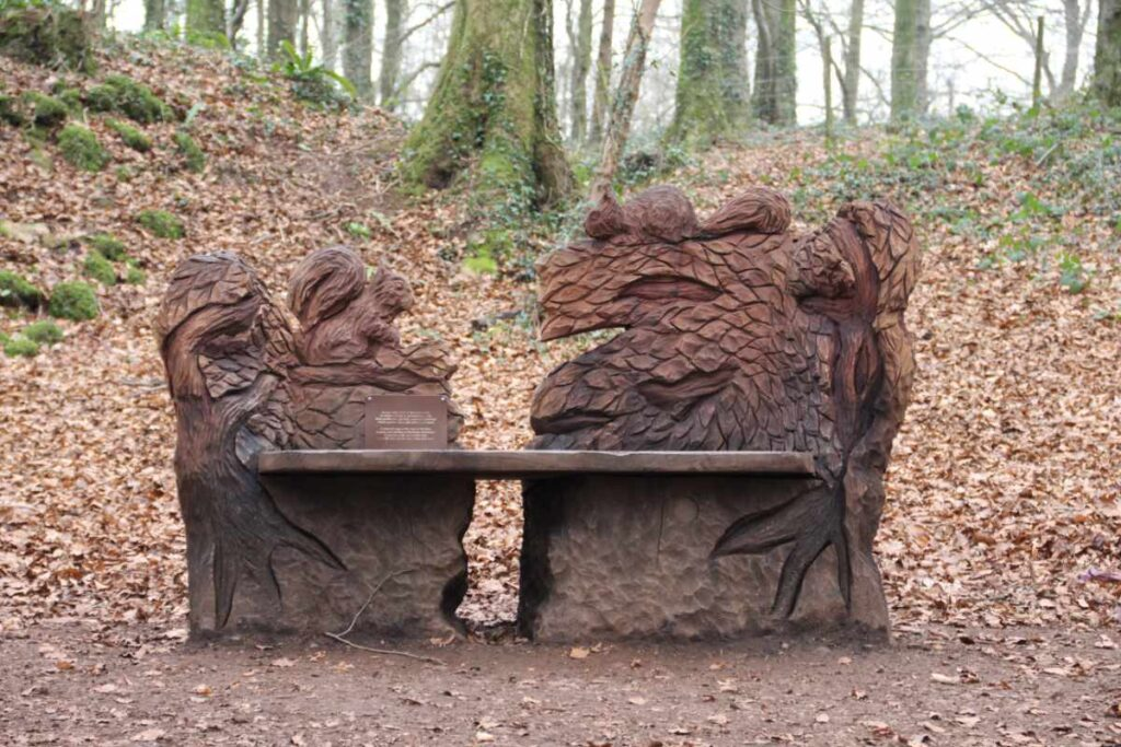 Wooden sculpture of a bench with squirrels around it