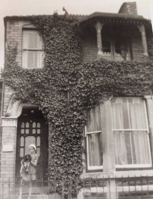 Photo of house with girl holding a dog, taken in 1928